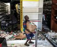 A young boy collects food and drinks from a burnt down and looted Auchan supermarket in an upscale Dakar neighbourhood.  By JOHN WESSELS (AFP)