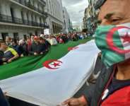Algerians marched with a giant national flag in the capital Algiers during a demonstration held by the Hirak pro-democracy movement, which last month revived weekly protests that been suspended for almost a year due to the coronavirus pandemic.  By RYAD KRAMDI (AFP)