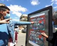 Libyans look at a poster depicting members of the family that commanded a militia that traumatised Tarhuna town.  By Mahmud Turkia (AFP)