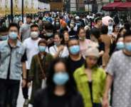Many people in Wuhan, where the coronavirus first emerged, are still wearing masks despite there being no new cases since May.  By Hector RETAMAL (AFP)