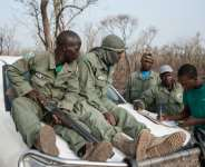 Researcher Martial Kiki (right) fills in data sheets with rangers during a lion population estimate at Nigeria's Yankari Game Reserve.  By Stefan Heunis (AFP/File)