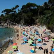 People enjoy a day out at the beach in Platja D'Aro near Girona -- Spaniards endured one of the world's toughest lockdowns for three months from March 2020.  By Josep LAGO (AFP)