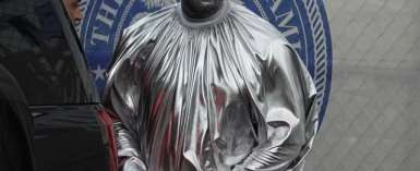 Kanye West wears silver body paint and a billowing silver robe as he appears at his latest opera in Miami. (MEGA)