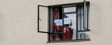 A man in mandatory quarantine in Kenya holds a sign reading
