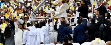 Many of the faithful wore pope-emblazoned white and yellow caps -- the colours of the Vatican, and cheered as the pope-mobile made its way through wind-swept clouds of red dust.  By Tiziana FABI (AFP)