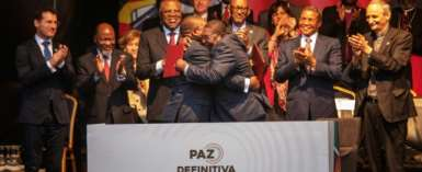 Mozambique's President Filipe Nyusi and Renamo leader Ossufo Momade hug after signing the landmark peace agreement on August 6.  By STRINGER (AFP/File)