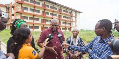 Former President Mahama talking to the media in front of one of the numerous abandoned projects in the new regions.