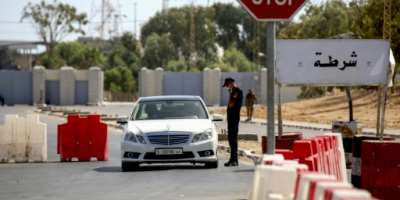 A Tunisian policeman checks a Libyan motorist at the Ras Jdeir border crossing between the two countries following its reopening after a two-month Covid closure.  By FATHI NASRI (AFP)