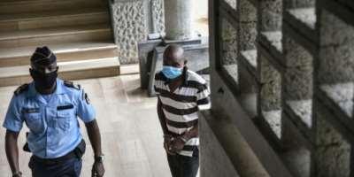 Amadé Oueremi (tee-shirt rayé), ancien chef de guerre et milicien accusé d'assassinats massifs dans l'Ouest de la Côte d'Ivoire en 2011, arrive à son procès à Abidjan, sous escorte policière, le 1er avil 2021..  By SIA KAMBOU (AFP)