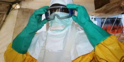 Ebola struggle: An Ebola fighter dons protective gear at a hospital in Conakry (2014 file picture).  By CELLOU BINANI (AFP/File)