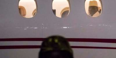 Former president Yaya Jammeh, The Gambia's leader for 22 years, looks through a window from a plane as he leaves the country on January 21, 2017.  By STRINGER (AFP)