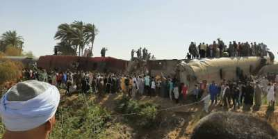 People gather on and around the wreckage of two trains that collided in the Tahta district of Sohag province, some 460 kms south of the Egyptian capital Cairo on March 26.  By - (AFP/File)