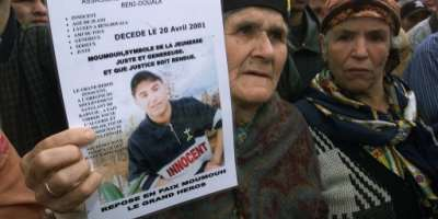 The grandmother of Massinissa Guermah, a teenager killed by Algerian  police in April 2001, holds aloft his picture in May that year, amid protests in the country's Berber heartland.  By - (AFP/File)