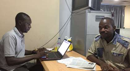 Hamza Idris (left), an editor with the Daily Trust newspaper, sits with colleague Hussaini Garba Mohammed in their office in the Nigerian capital, Abuja, in February 2019. The office was raided in January by the military, who seized 24 computers. (CPJ/Jonathan Rozen)
