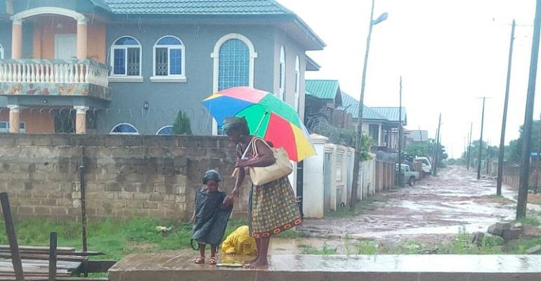 A Mother journey through rain to take her kids to school
