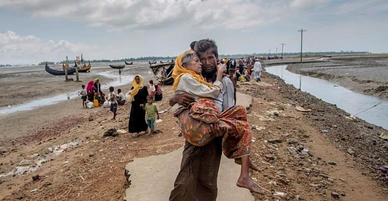 Abdul Kareem, a Rohingya Muslim, carries his mother, Alima Khatoon, to a refugee camp after crossing from Burma into Bangladesh on Sept. 16, 2017. © 2017 Dar Yasin/AP