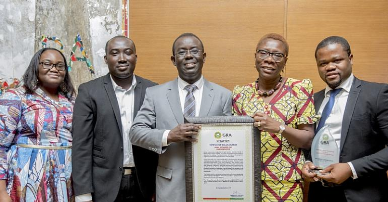 Kwame Addo-Kufuor, Regional Chief Financial Officer, Newmont Africa (Middle) and Adiki Ayitevie, Snr Director Communications and External Relations, Newmont Africa with the citation