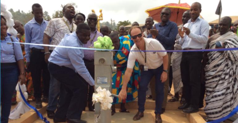 From Left Mr. Ebenezer Faulkner, Nana Agyei Duku Ababio II And Mr. Kenneth Norris Pumping The Water To Officially Commission The Borehole