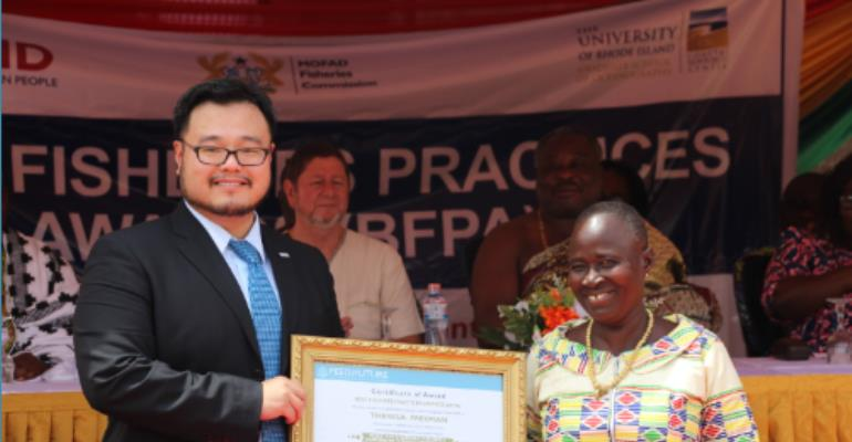 """USAID/Ghana Private Sector Team Lead Richard Chen awards Theresa Freeman with the title of """"Most Outstanding Fisheries Leadership in Fish Processing"""" at Feed the Future's awards ceremony to honor those who work to protect Ghana's fishing industry. Photo credit: Priscilla Addison, USAID/Ghana"""