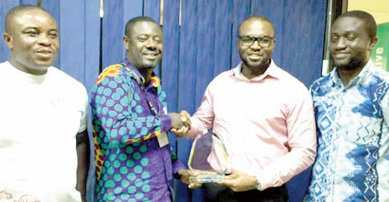 Eric Asante (2nd right) presenting the award to Gabriel Opoku- Asare. With them representatives of GGBL
