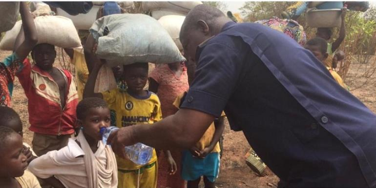 Chereponi District Police Commander, ASP Henry Amankwah Tia providing water to thisty children fleeing the community.