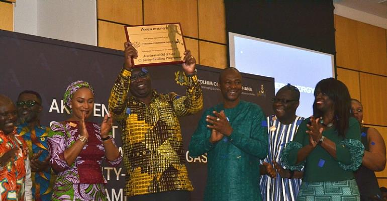 Mr. Egbert Faibille Jnr. Acting CEO of Petroleum Commission displays the plaque symbolising the commencement of Aker Energy's support for the AOGC Programme at the Announcement ceremony as Her Excellency Hajia Samira Bawumia Deputy Energy Minister and some Board members look on