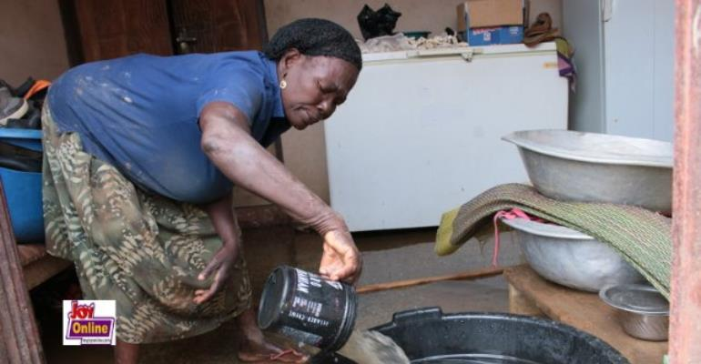 A flood victim scoops water from her house.