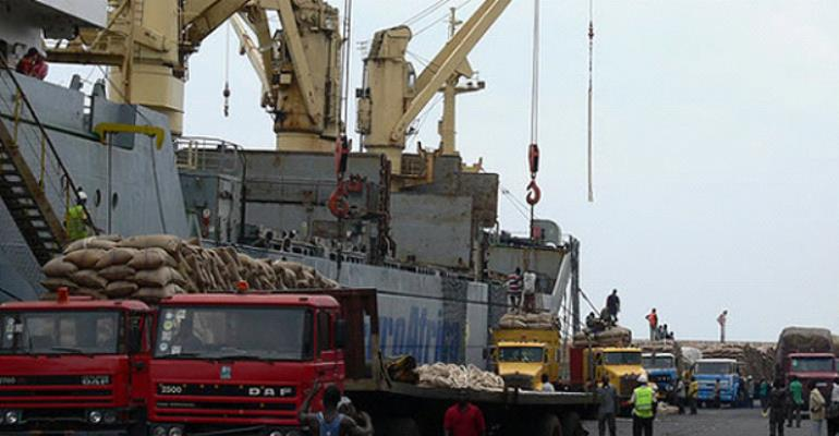 Trucks offloading sacks of raw cocoa beans onto vessels at Tema