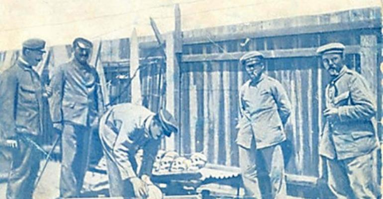German soldiers loading human skulls and bones of massacred Hereros into a casket for shipping to German universities, especially, Berlin