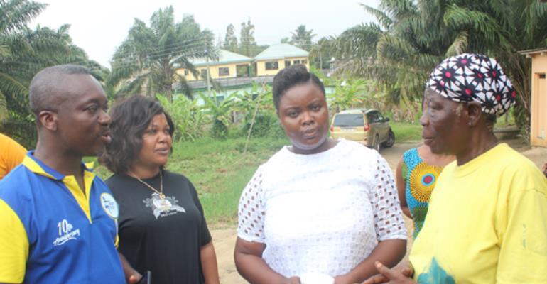 Mr Okyere-Apenteng (left) interacting with Madama Abiba Fuseini as some club members look on