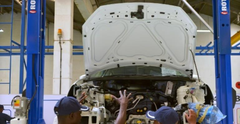 Technicians work on a Polo Vivo at a new assembly plant in Kenya's Thika industrial area, on December 21, 2016.  By Tony Karumba (AFP/File)