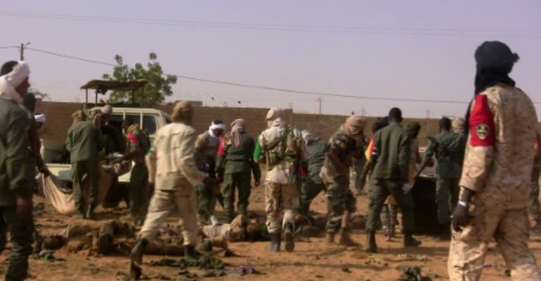 The dead and injured are evacuated following a suicide bomb attack that ripped through a camp grouping former rebels and pro-government militia in Gao, in northern Mali.  By STRINGER (AFP)