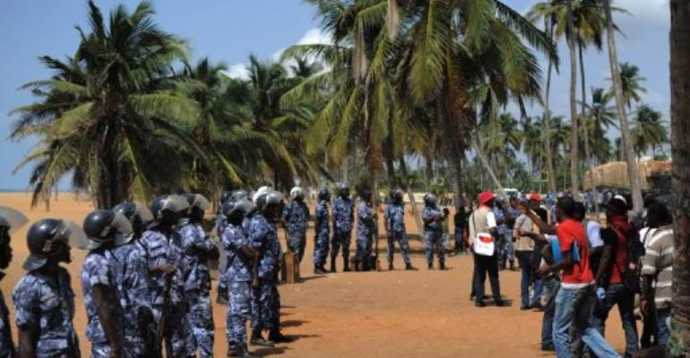 Opposition supporters face police officers after trying to hold a sit-in near the presidency in Lome on March 14, 2013.  By Daniel Hayduk (AFP/File)