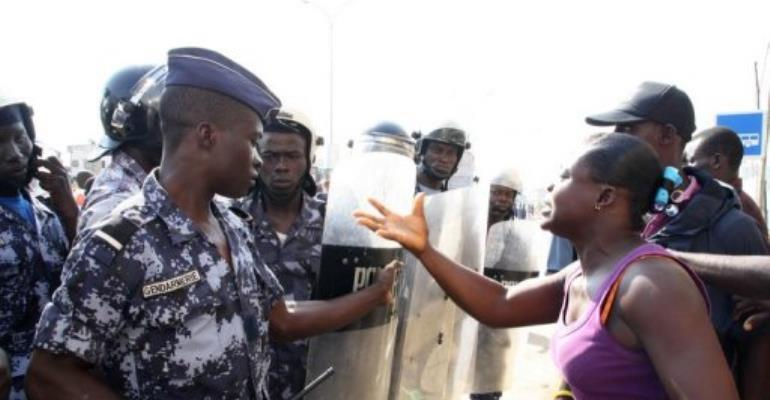 A woman talks to police officers as they patrol near a meeting of''Let's Save the Togo''.  By Emile Kouton (AFP/File)