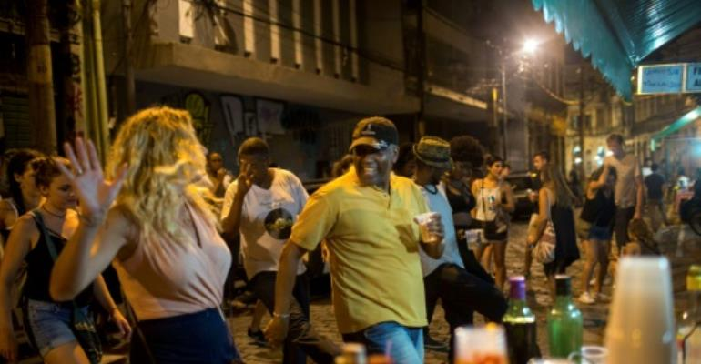 Tourists and locals dance to funk music in Pedra do Sal, located in downtown Rio near the port, where many slaves went soon after arriving on ships from Africa.  By MAURO PIMENTEL (AFP)