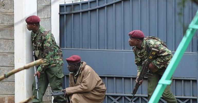 Armed Kenyan policemen take cover outside the Westgate mall in Nairobi on September 23, 2013.  By Simon Maina (AFP)
