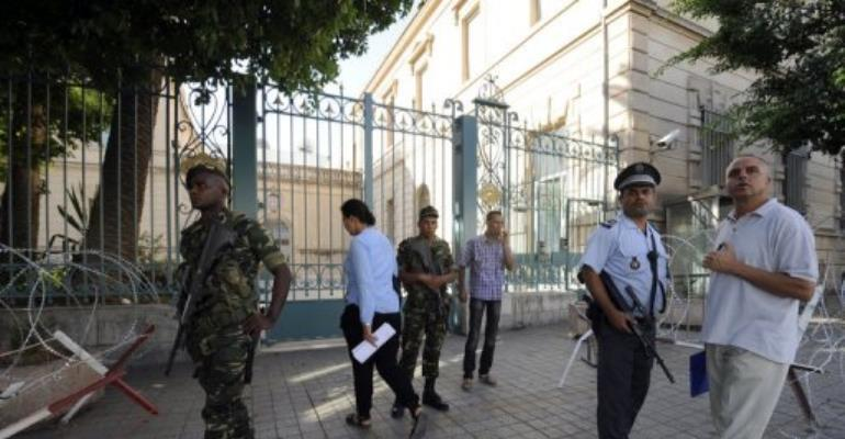 Tunisian police and soldiers stand guard in front of the French ambassy in Tunis.  By Fethi Belaid (AFP)