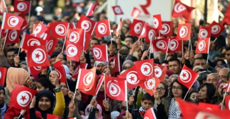 Tunisians wave national flags and shout slogans on January 14, 2016, during a rally to mark the fifth anniversary of the 2011 revolution.  By Fethi Belaid (AFP/File)