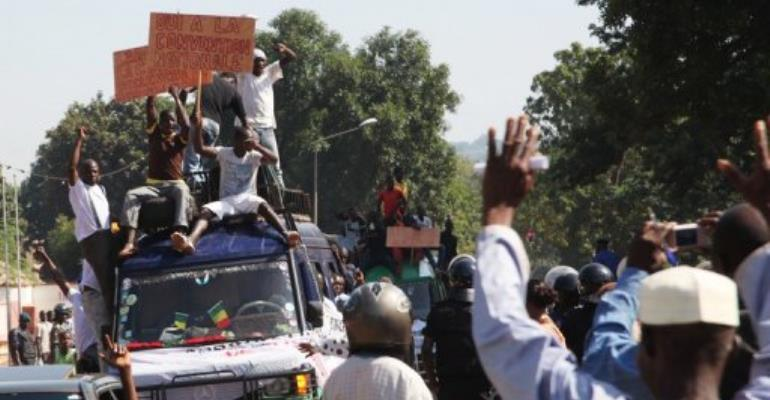 People hold banners and sit on a truck during a protest against a foreign military intervention in Mali.  By Habibou Kouyate (AFP/File)