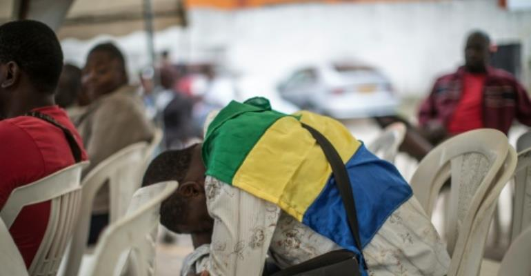 Wrapped in the Gabonese flag a supporter of the opposition candidate Jean Ping on August 31, 2016 at the party headquarters, waiting for results in the country's presidential election.  By Marco Longari (AFP)