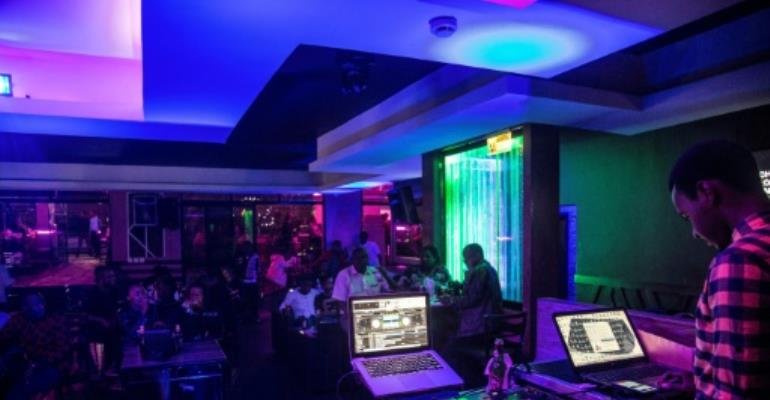 Young people enjoy the night life at the Fuschia Bar in Rwanda's capital Kigali. Many youths feel the absence of close kin they could never know, cut down in the three-month genocide.  By JACQUES NKINZINGABO (AFP)