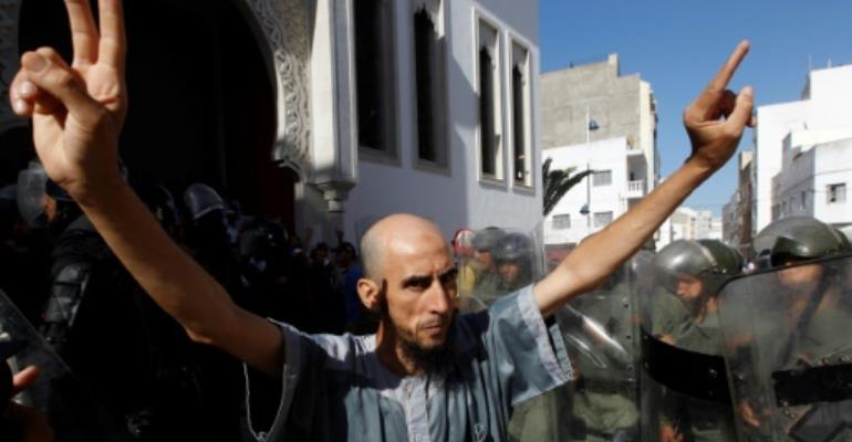 A demonstrator gestures in front of Moroccan security forces during a march in defiance of a government ban in the northern Moroccan city of Al-Hoceima on July 20, 2017.  By STRINGER (AFP)