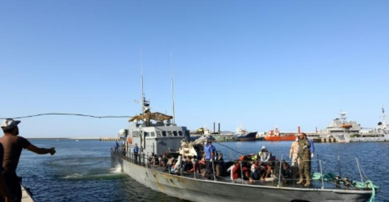 A file picture taken on October 11, 2017 shows the Libyan coastguard bringing African migrants to a naval base in the capital Tripoli after rescuing them from a rubber boat off Sabratha.  By MAHMUD TURKIA (AFP/File)
