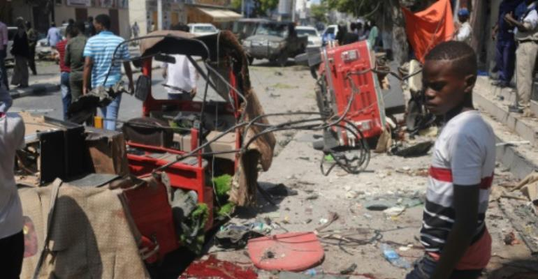 A Somali boy walks near blood-stains and debris on the ground after an explosion outside a restaurant in Mogadishu that left at least 15 people dead.  By MOHAMED ABDIWAHAB (AFP)