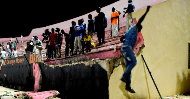 A wall collapsed onto fans fleeing the stadium to escape the hail of projectiles, with some crushed in the panic. Eight people died and dozens more were injured in the crush.  By SEYLLOU (AFP/File)