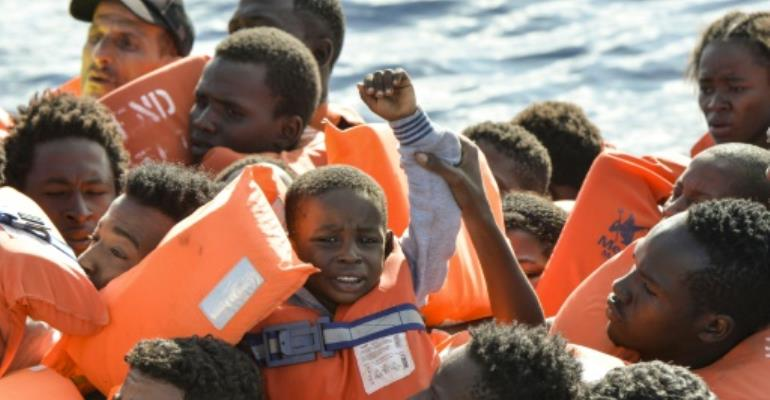 A young boy is seen among the migrants and refugees seated on a rubber boat and waiting to be rescued by the Topaz Responder, a rescue ship run by Maltese NGO