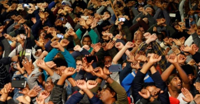 African migrants and Israelis with their hands crossed in the Israeli coastal city of Tel Aviv on February 24, 2018 rally against the government's policy to forcibly deport African refugees and asylum seekers.  By JACK GUEZ (AFP)