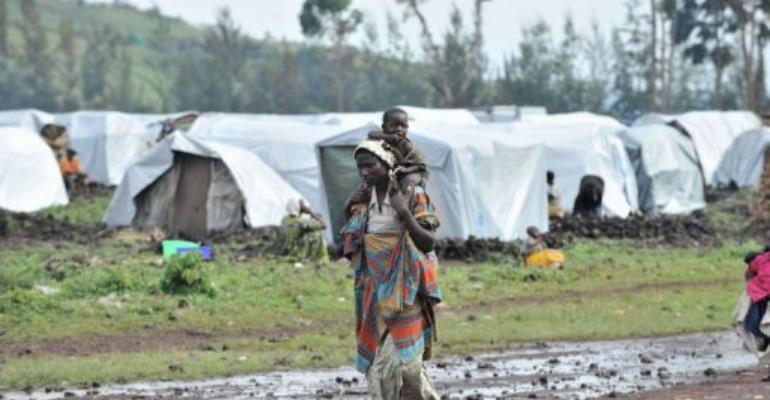 A woman walks with her child on October 15, 2012 in the Kanyaruchinya camp for internally displaced people, near Goma.  By Junior D. Kannah (AFP/File)