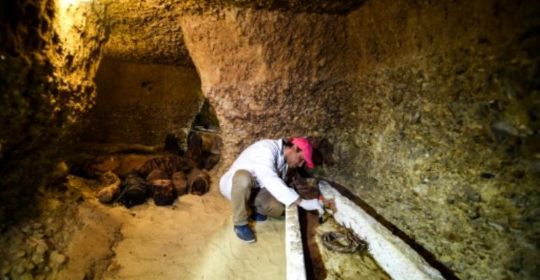 An archaeologist brushes a newly-discovered mummy laid inside a sarcophagus, part of a collection found in burial chambers dating to the Ptolemaic era (323-30 BC) in February 2019.  By MOHAMED EL-SHAHED (AFP/File)