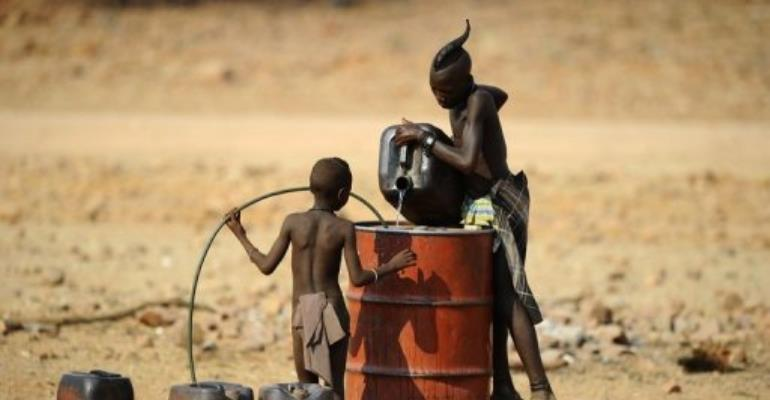 Two Himba boys pour water into a tank in 2010 in the village of Okapare, near Opuwo in northern Namibia.  By Stephane de Sakutin (AFP/File)